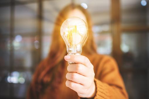 電球アイデアを持つ女性|アインの集客マーケティングブログ
