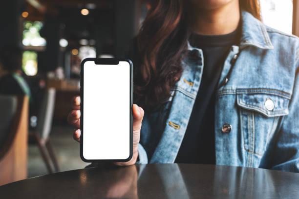 eine Frau hält und zeigt schwarzes Handy mit leerem Bildschirm im Café – Foto