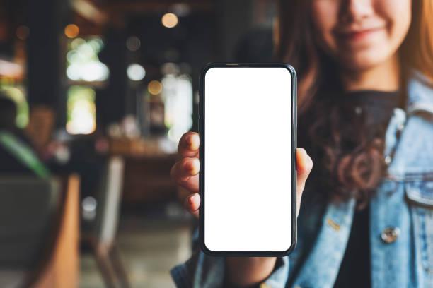 eine Frau hält und zeigt schwarzes Handy mit leerem weißen Bildschirm im Café – Foto