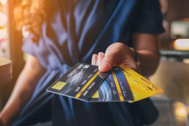 eine Frau, die Kreditkarten hält und zeigt – Foto