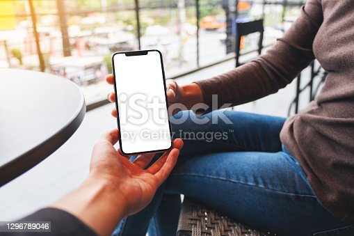 Mockup image of a woman holding and showing white mobile phone with blank black desktop screen to her friend