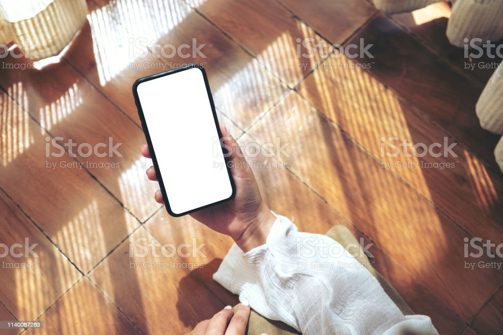 Top view mockup image of a woman holding and using black mobile phone...