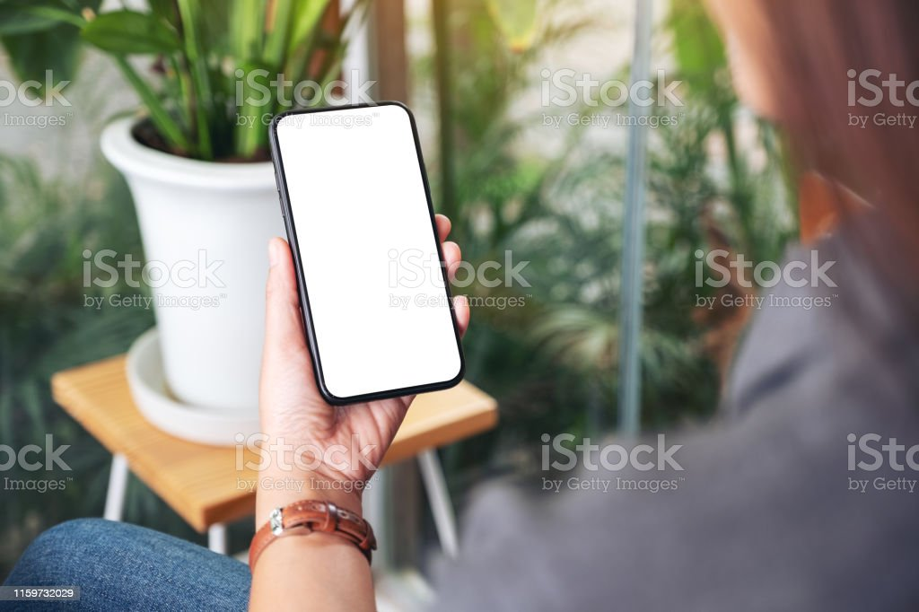 Mockup image of a woman holding and using black mobile phone with...
