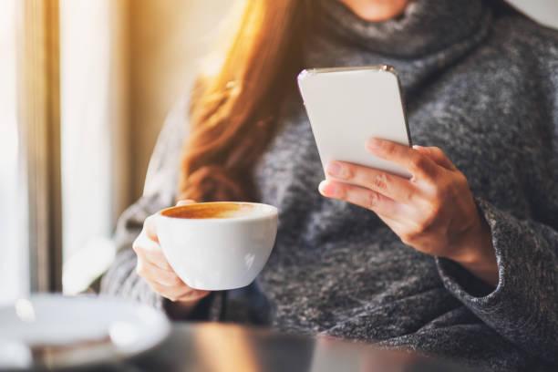 eine Frau hält und benutzt Mobiltelefon, während sie Kaffee im Café trinkt – Foto