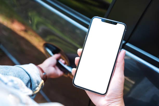 eine Frau, die beim Öffnen der Autotür mobiltelefon mit leerem Bildschirm hält und benutzt – Foto