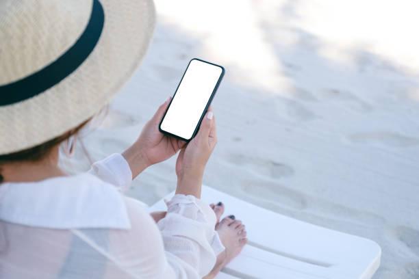 a woman holding black mobile phone with blank desktop screen - phone, travelling, copy space imagens e fotografias de stock