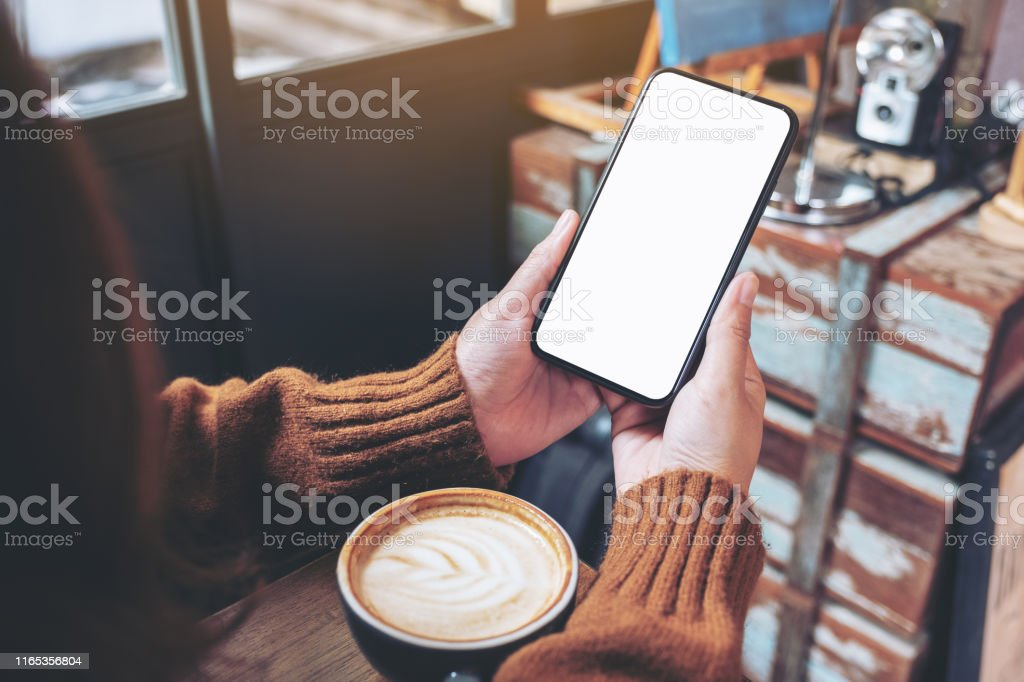 Mockup image of a woman holding black mobile phone with blank desktop...