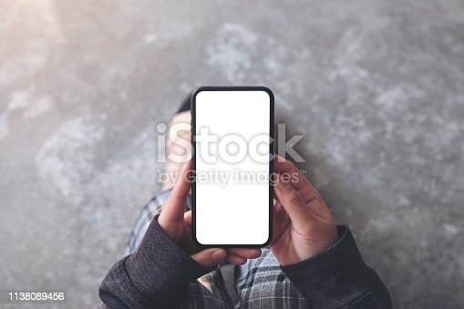 Top view mockup image of a woman holding black mobile phone with blank desktop screen while sitting on the floor