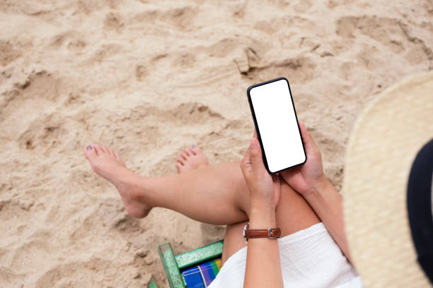 a woman holding black mobile phone with blank desktop screen while sitting on a beach chair - phone, travelling, copy space imagens e fotografias de stock