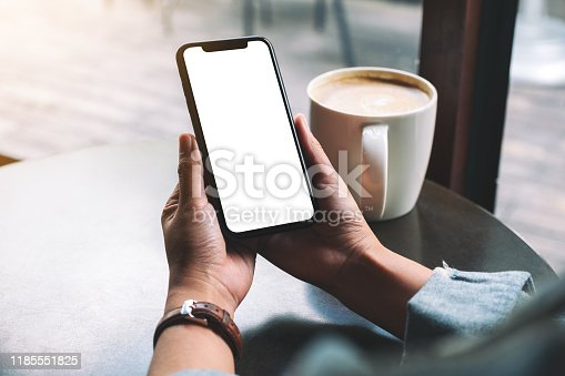 Mockup image of a woman holding black mobile phone with blank screen with coffee cup on wooden table