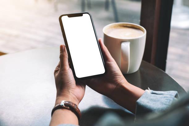 eine Frau hält schwarzes Handy mit leerem Bildschirm mit Kaffeetasse auf Holztisch – Foto