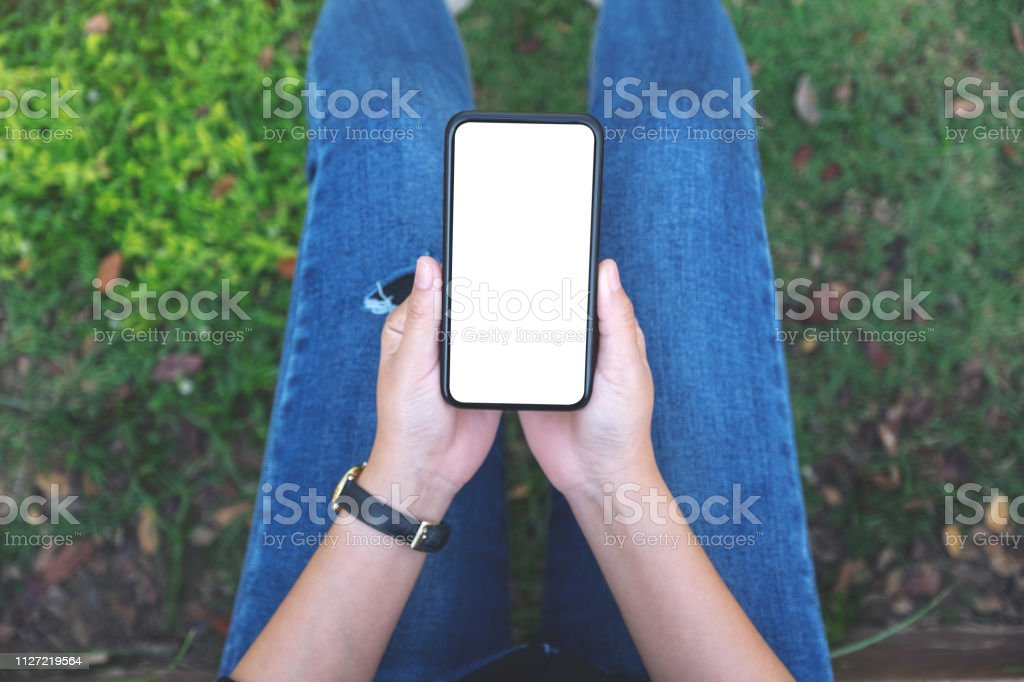 Top view mockup image of a woman holding black mobile phone with...