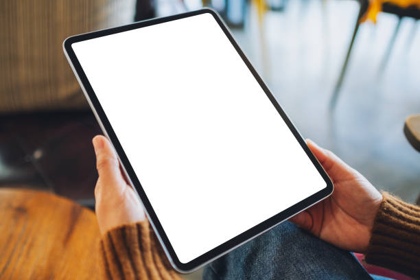 a woman holding black tablet pc with blank white screen on wooden table Mockup image of a woman holding black tablet pc with blank white screen on wooden table ipad stock pictures, royalty-free photos & images