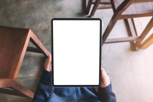 eine Frau hält schwarzen Tablet-PC mit leerem weißen Bildschirm, während sie im Café sitzt – Foto