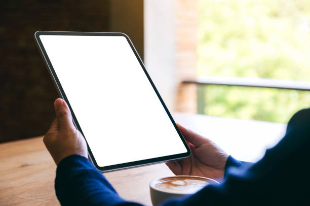 eine Frau hält schwarzen Tablet-PC mit leerem weißen Bildschirm mit Kaffeetasse auf Holztisch – Foto