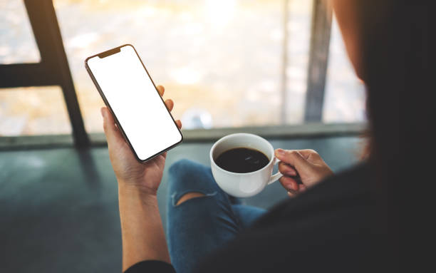 eine Frau hält Handy mit leerem Bildschirm beim Kaffeetrinken – Foto