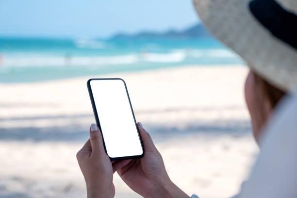 a woman holding white mobile phone with blank desktop screen - phone, travelling, copy space imagens e fotografias de stock