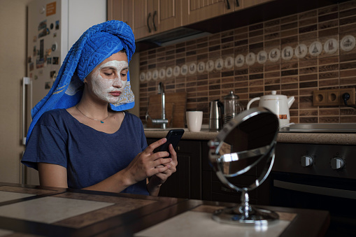 istock a woman in a blue towel on her head speaks via video link on a smartphone 1253271843