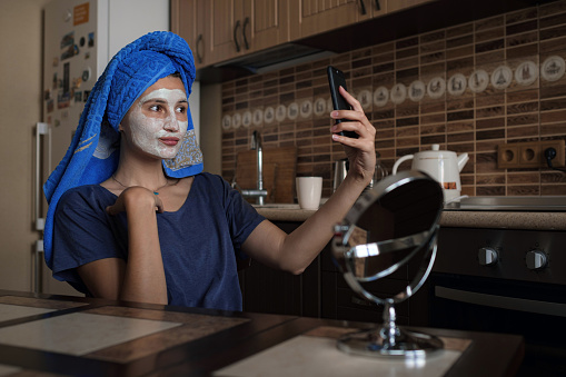 istock a woman in a blue towel on her head speaks via video link on a smartphone 1253272506