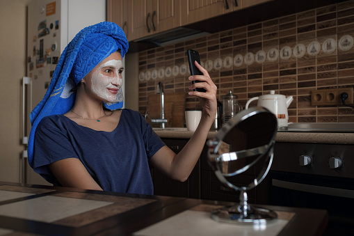 istock a woman in a blue towel on her head speaks via video link on a smartphone 1253272523