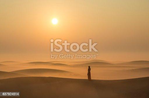 A woman in a mist in desert landscape at Sunraise near Dubai, UAE