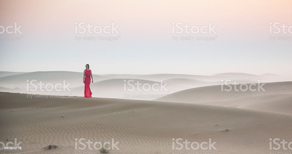 a woman in a desert at sunrise near Dubai stock photo