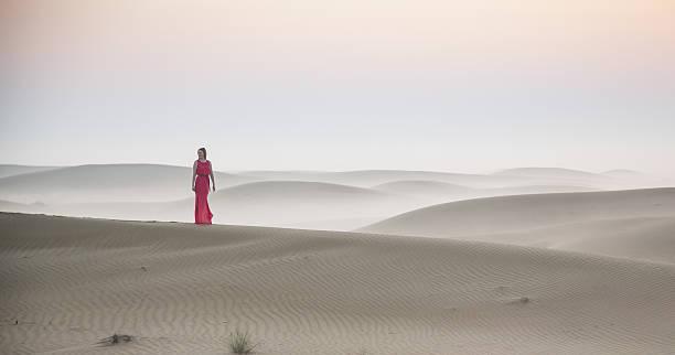 a woman in a desert at sunrise near Dubai stock photo