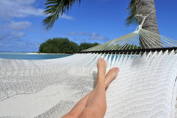 pov of a woman lay on a hammock relaxing in muri lagoon in rarotonga cook islands - woman leg beach pov stock photos and pictures