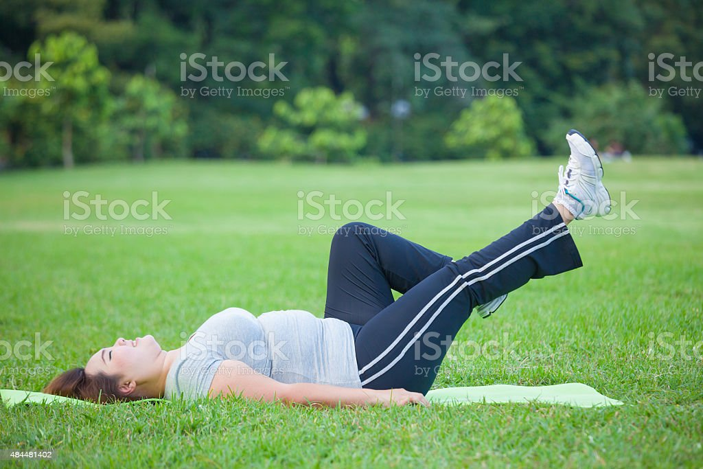 a woman lying by exercise leg upwards圖像檔