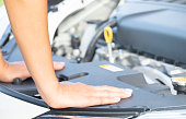 istock a woman maintenance a car. hands a women on the engine room and looking for something wrong on her car. 1034123288