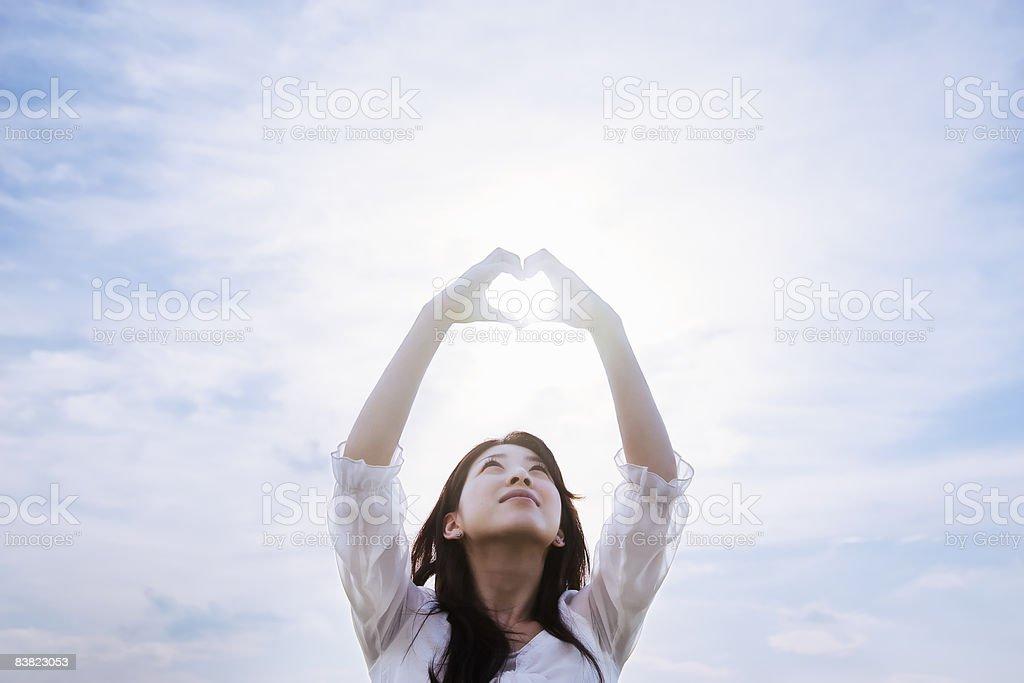 a woman making a heart by hands under a sky zbiór zdjęć royalty-free