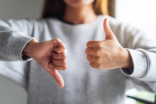 Closeup image of a woman making thumbs up and thumbs down hands sign