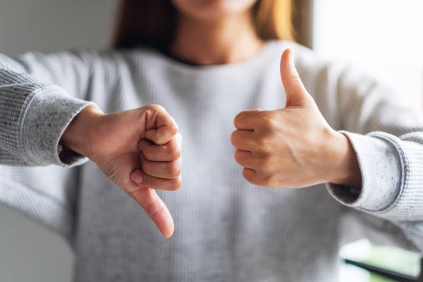a woman making thumbs up and thumbs down hands sign - feedback icon imagens e fotografias de stock