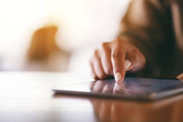 Eine Frau, die mit dem Finger auf den Tabletten-Pc auf den Holztisch zeigt – Foto
