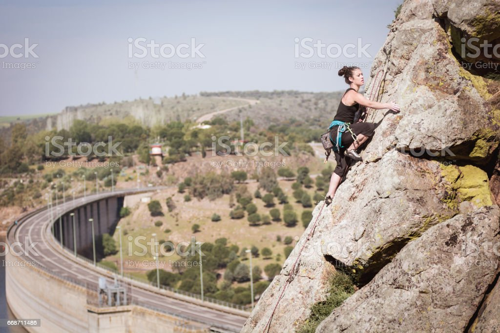 a woman practicing climbing on a mountain of rocks, water dam stock photo