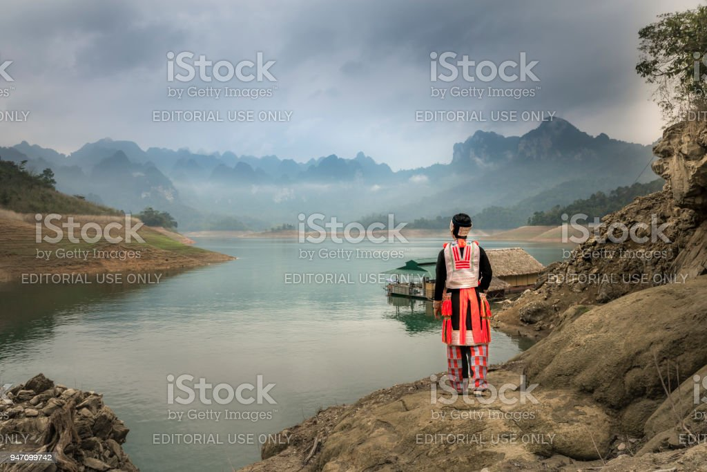 a woman Red Dao ethnic minority watching the majestic beauty of the rocky mountain's limestone and lakes stock photo