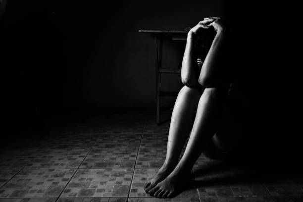 a woman sitting on ground with arm around lower head, sexual violence , sexual abuse, human trafficking concept stock photo