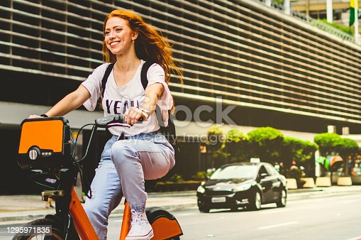a young woman with red hair, on the cycle path of avenue paulista
