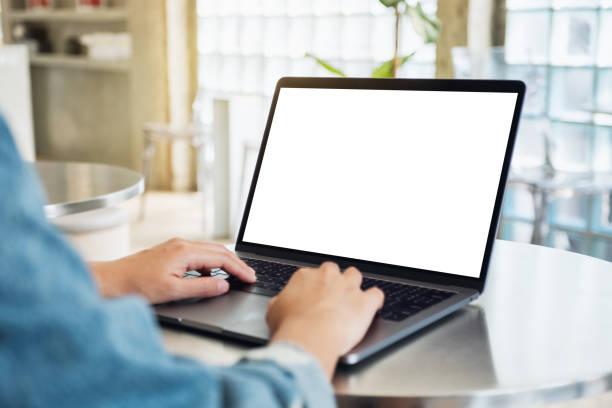 Eine Frau, die einen Laptop-Computer mit leerem weißem Desktop-Bildschirm verwendet und eingibt – Foto