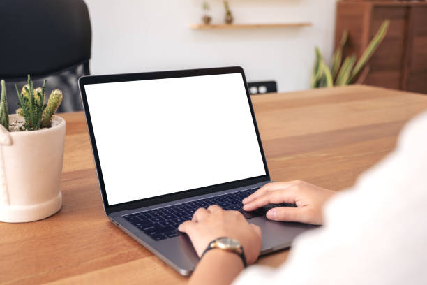a woman using and typing on laptop with blank white desktop screen - white background стоковые фото и изображения