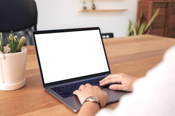 a woman using and typing on laptop with blank white desktop screen - white background zdjęcia i obrazy z banku zdjęć