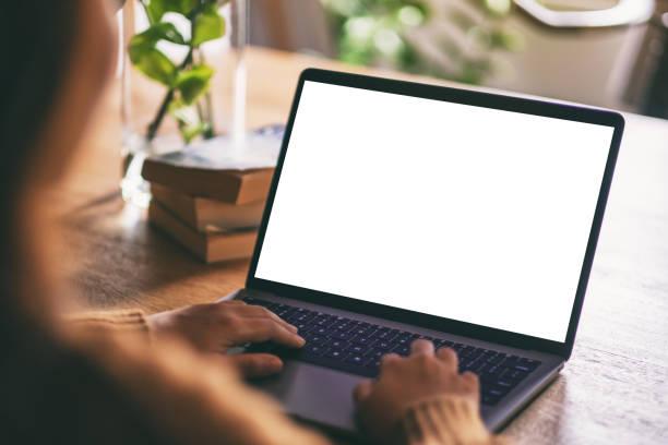 uma mulher que usa e que datilografa no portátil com tela branca em branco do desktop - laptop - fotografias e filmes do acervo