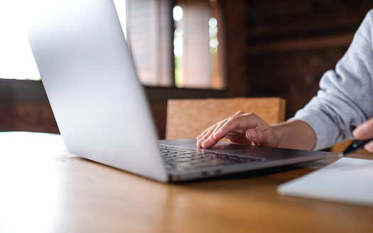 Closeup image of a woman working and touching on laptop touchpad on the table