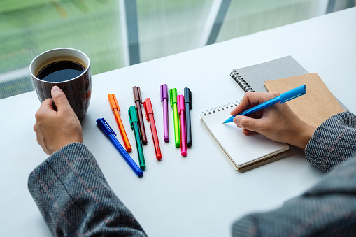 818512928 istock photo a woman writing on a blank notebook with colored pens while drinking coffee 1224097467