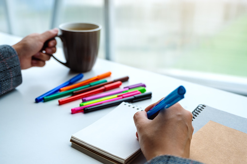 818512928 istock photo a woman writing on a blank notebook with colored pens while drinking coffee 1224097494