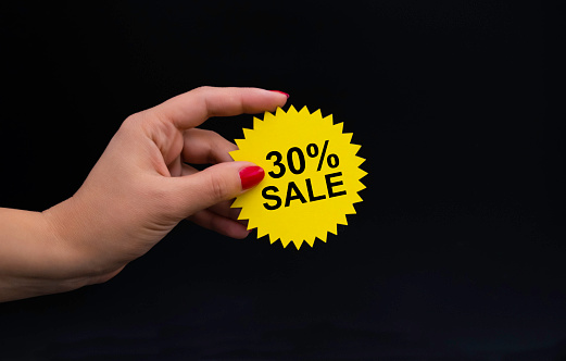 a woman's hand holds a yellow sticker with the inscription discount, a layout with a copy space on the theme of Black Friday. High quality photo