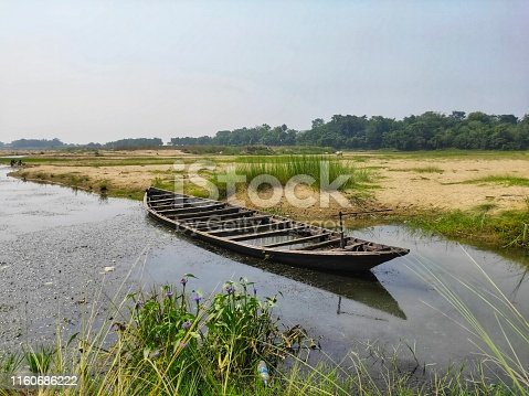 a wooden boat damped on the river side.