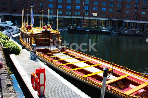 a wooden gondola covered in gold to soak on the banks of the river thames in uk