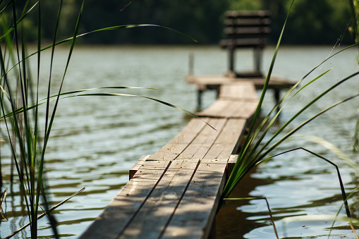 a wooden pier on a lake with a fishing chair