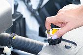 istock a wooman maintenance a car.  Check the car coolant level. 1030222544